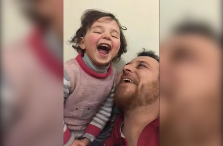 Amor de padre: en medio de un bombardeo, enseña a su hija a reír y así evitar que la pequeña tenga miedo