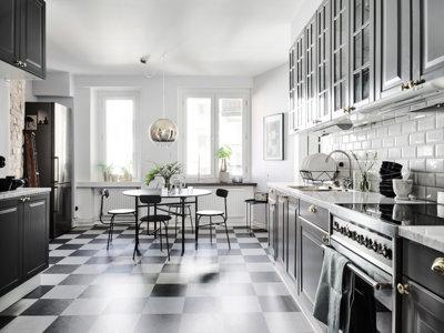 Un apartamento con cocina de mármol, ladrillo visto y suelo ajedrezado