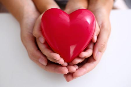 Manos del padre y la madre sosteniendo un corazón