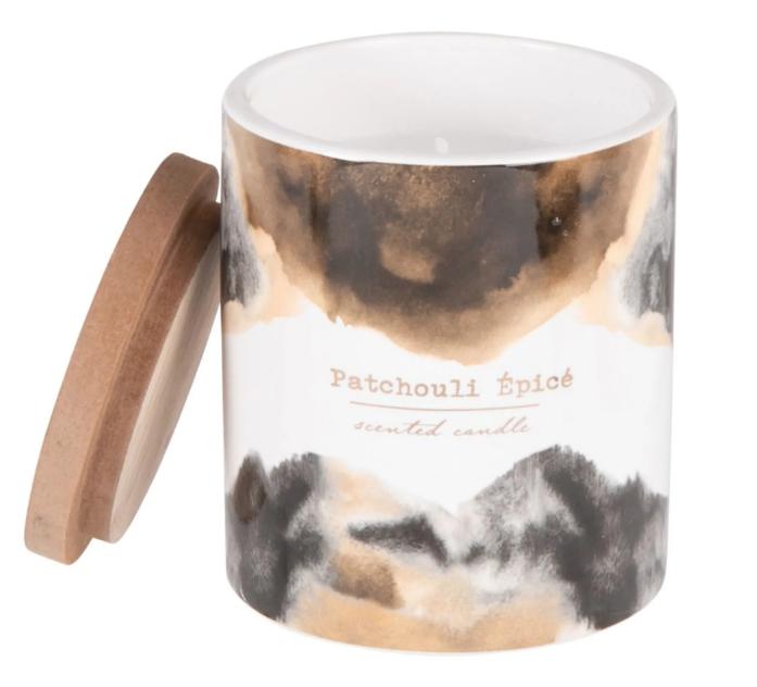 Vela perfumada en tarro de cerámica marrón, negra, blanca y dorada