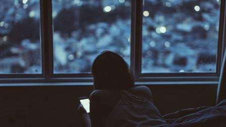 Una mujer mira su amovible junto a una ventana.