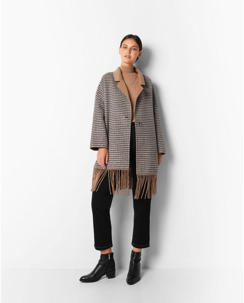Abrigo reversible confeccionado en mezcla de lana. Tipo oversize, viene con el cuello de solapas y cierre con un botón. Además, es de manga larga con hombro caído y detalle de flecos en el bajo.