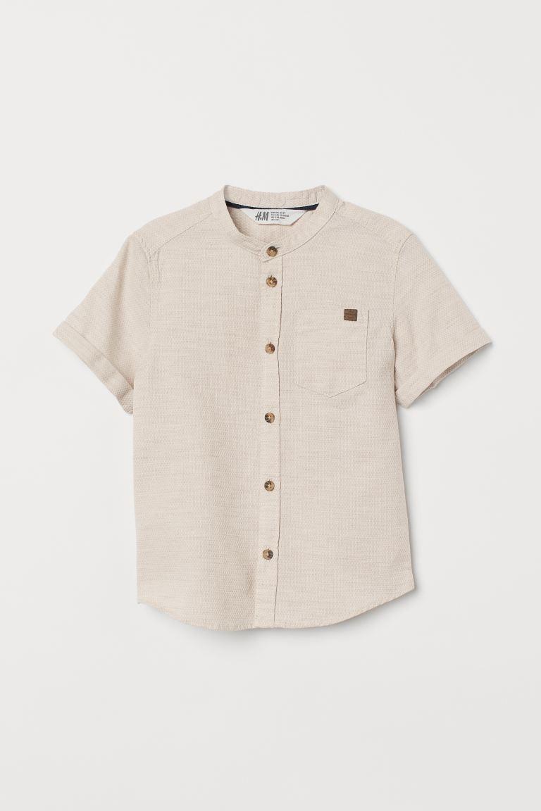 Camisa en algodón vaporoso con cuello mao, tapeta clásica y canesú en la espalda.