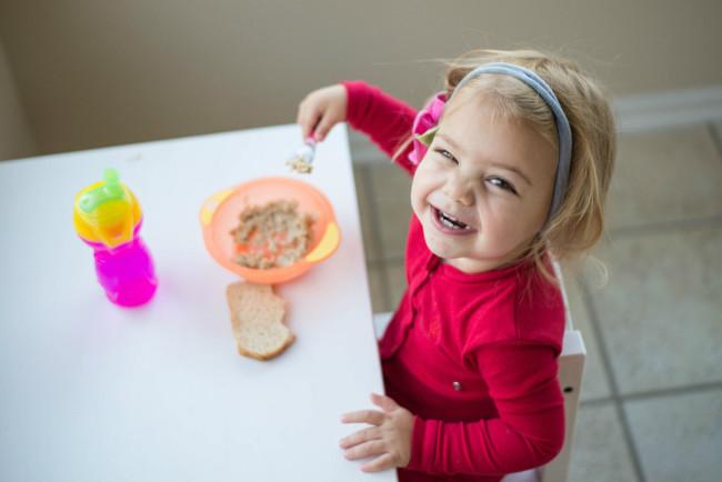 Una niña comiendo sola