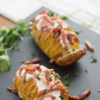 Patatas Hasselback gratinadas con queso cheddar y bacon. Receta de guarnición