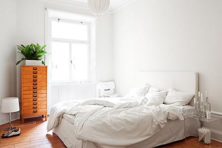 Dormitorio blanco con suelo de madera
