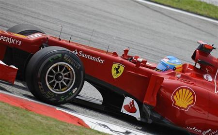 Fernando Alonso acepta el regalo de Sergio Pérez en el Gran Premio de Malasia