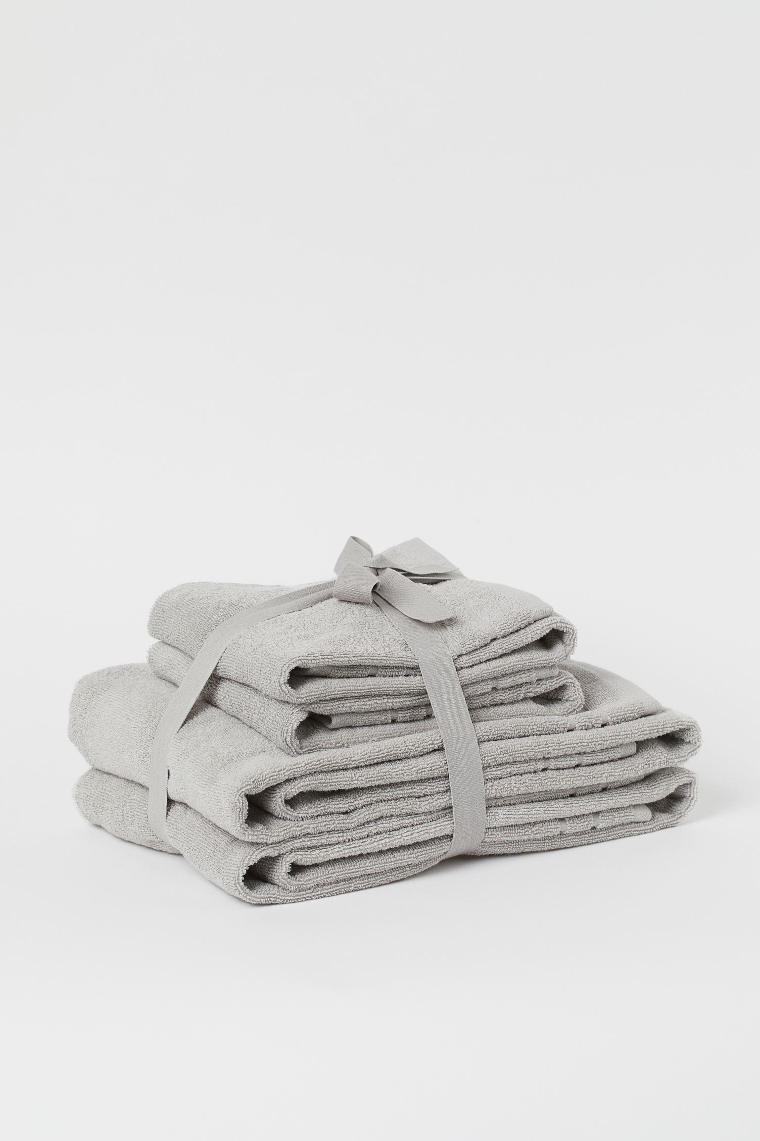 Juego de toallas en algodón rizado suave. Dos de mano y dos de baño, todas con colgador en un lateral.