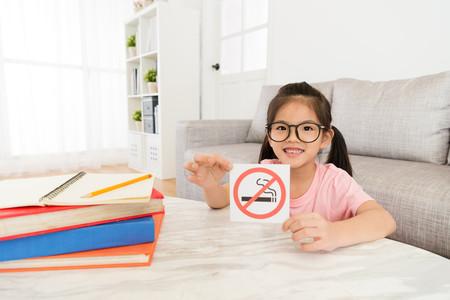 Niña con cartel Prohibido Fumar