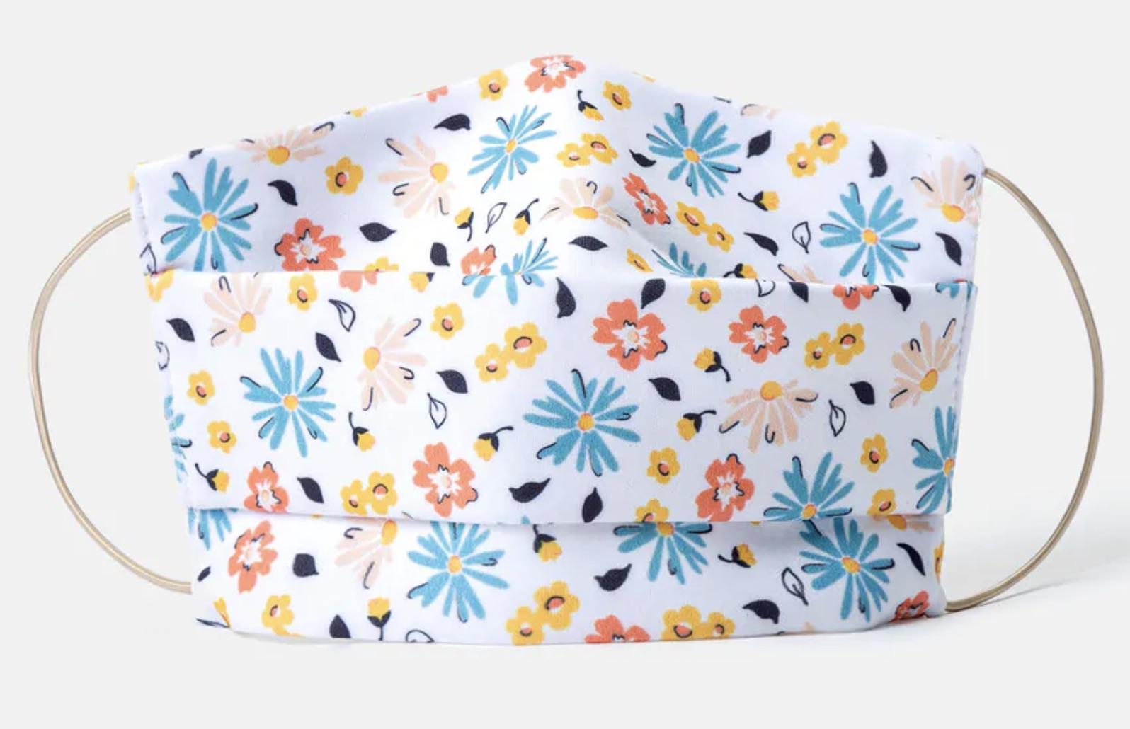 Mascarilla higiénica de tela lavable y reutilizable con estampado floral multicolor.