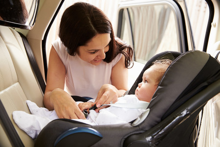 Madre colocando a su niño en silla a contramarcha en el coche