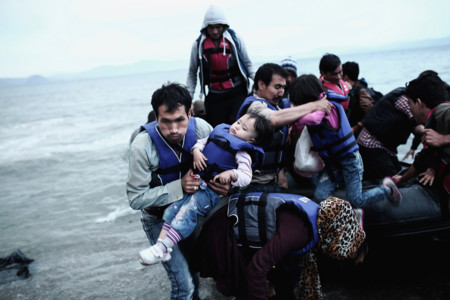 An Afghan Refugee Carries His Child As He Arrives Along With Others On A Beach On The Greek Island Of Kos After Crossing A Part Of The Aegean Sea Between Turkey And Greece On 27 May 2015angelos Tzortzinissony World Photography