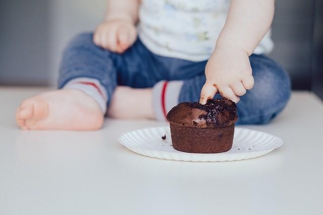 Bebé mete el dedo en un pastel de chocolate.