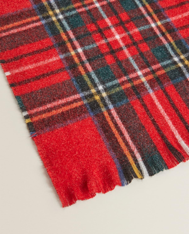 Manta con fondo rojo y diseño en forma de cuadros escoceses. Detalle de flecos en el borde
