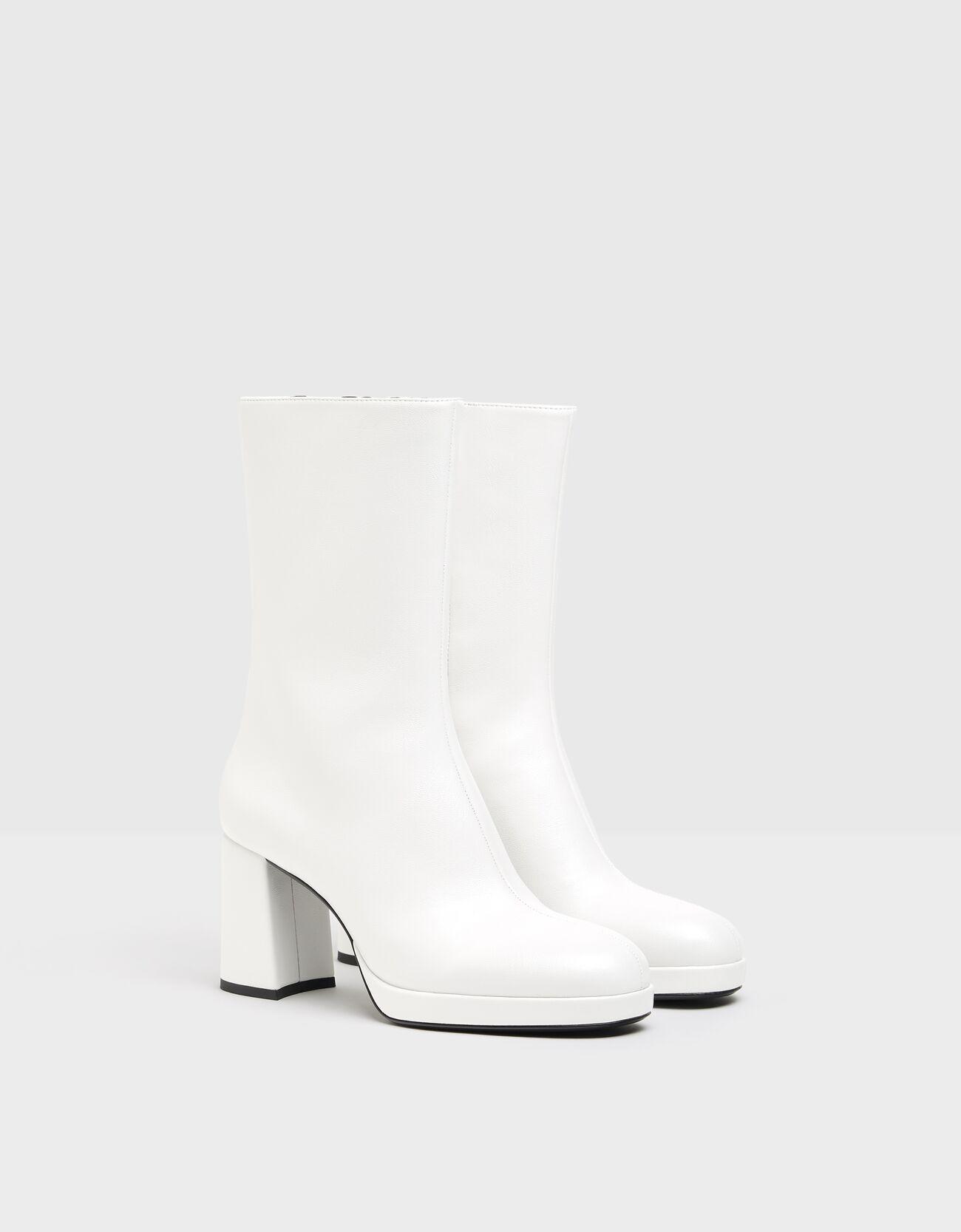 Botines tacón plataforma en color blanco. Cierre mediante cremallera. Caña alta. Elástico oculto para facilitar el calce.
