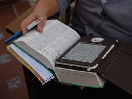 Un lector consulta un libro de papel y electrónico.
