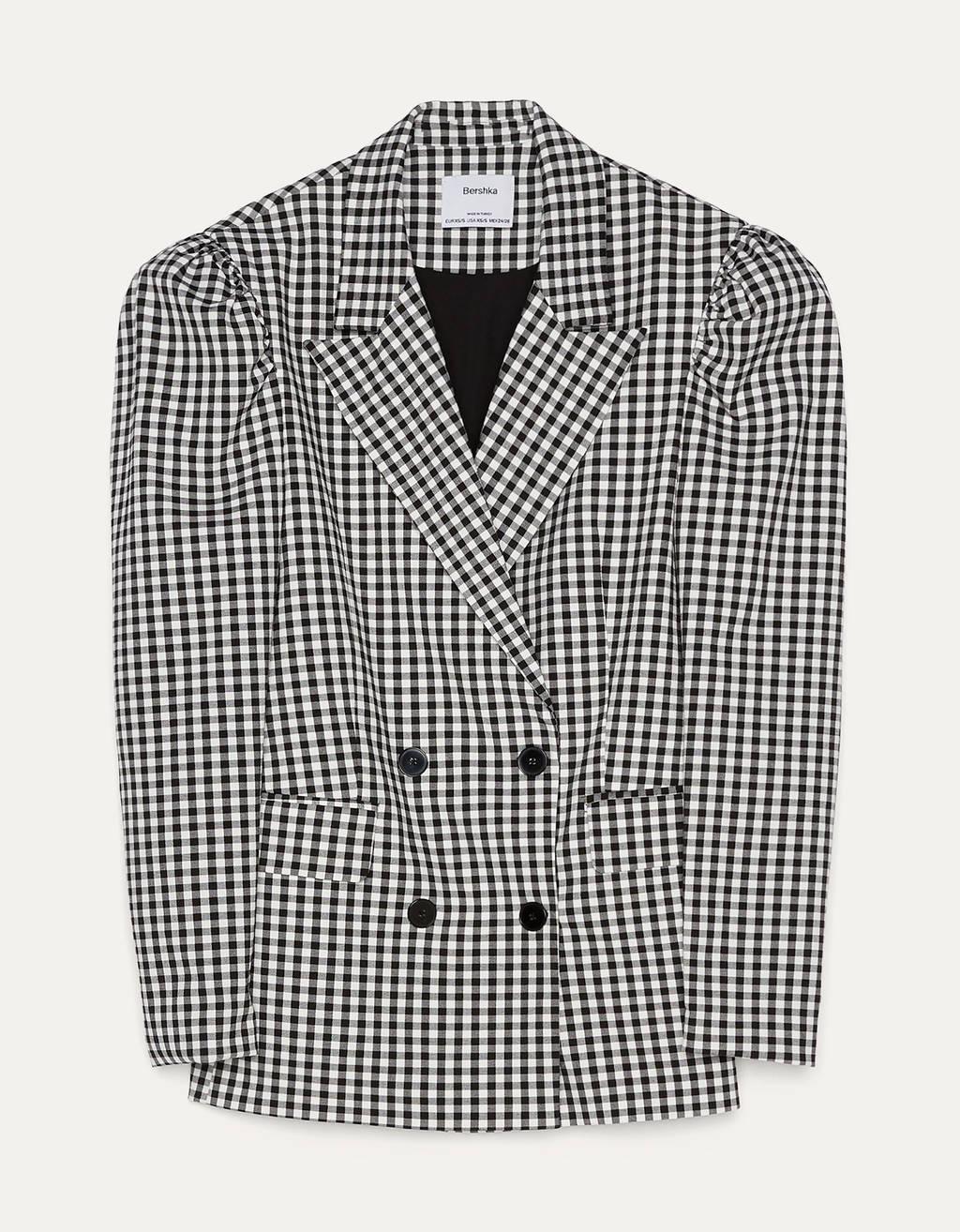 Blazer con cuadro vichy, cuello solapa y manga abullonada. Escote cruzado con botones y bolsillos.