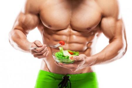 Cuerpo musculado comiendo ensalada