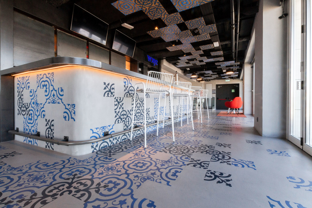 El cemento pulido estampado con grandes cenefas es el protagonista del bar de la azotea (con vistas) del hotel Aloft en Madrid
