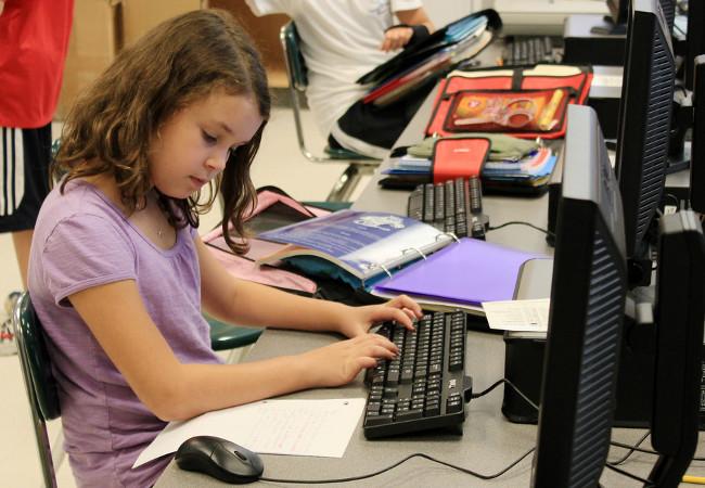 Niña usando el ordenador en clase