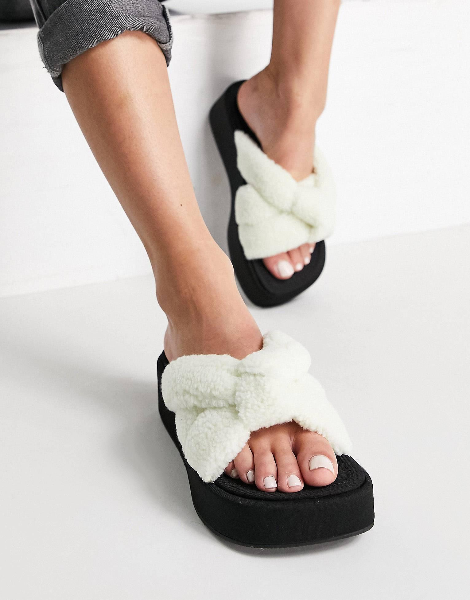 Sandalias color crema con plataforma plana y diseño acolchado y anudado de borreguito.
