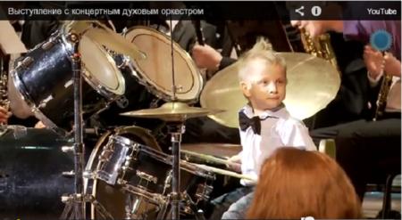 Niño ruso de tres años toca la batería en una orquesta