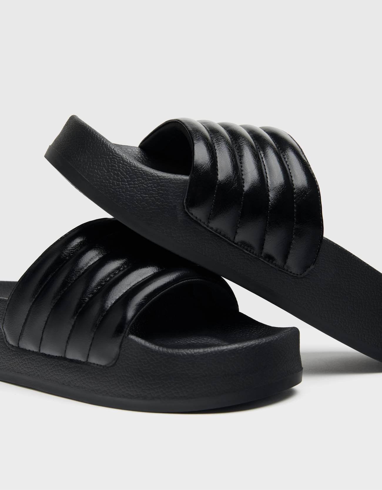 Sandalia plana en color negro. Detalle de acolchados. Suela con plataforma ligera.
