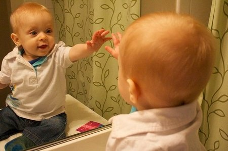Resultado de imagen de El niño del espejo le da a su amiguito reflejado la mano derecha y aquel, le saluda, con la izquierda.
