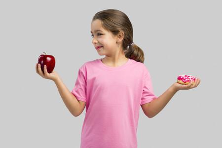Nina con una manzana y un donuts
