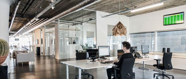 Una oficina con aire industrial mucho cristal y madera for Diseno oficinas industriales