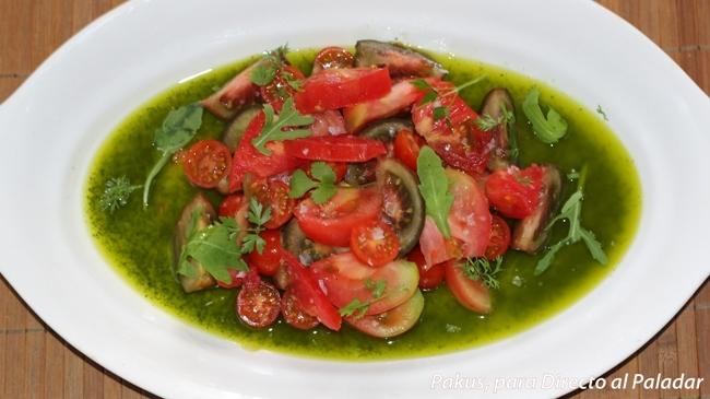 ensalada de tomates surtidos sobre albahaca