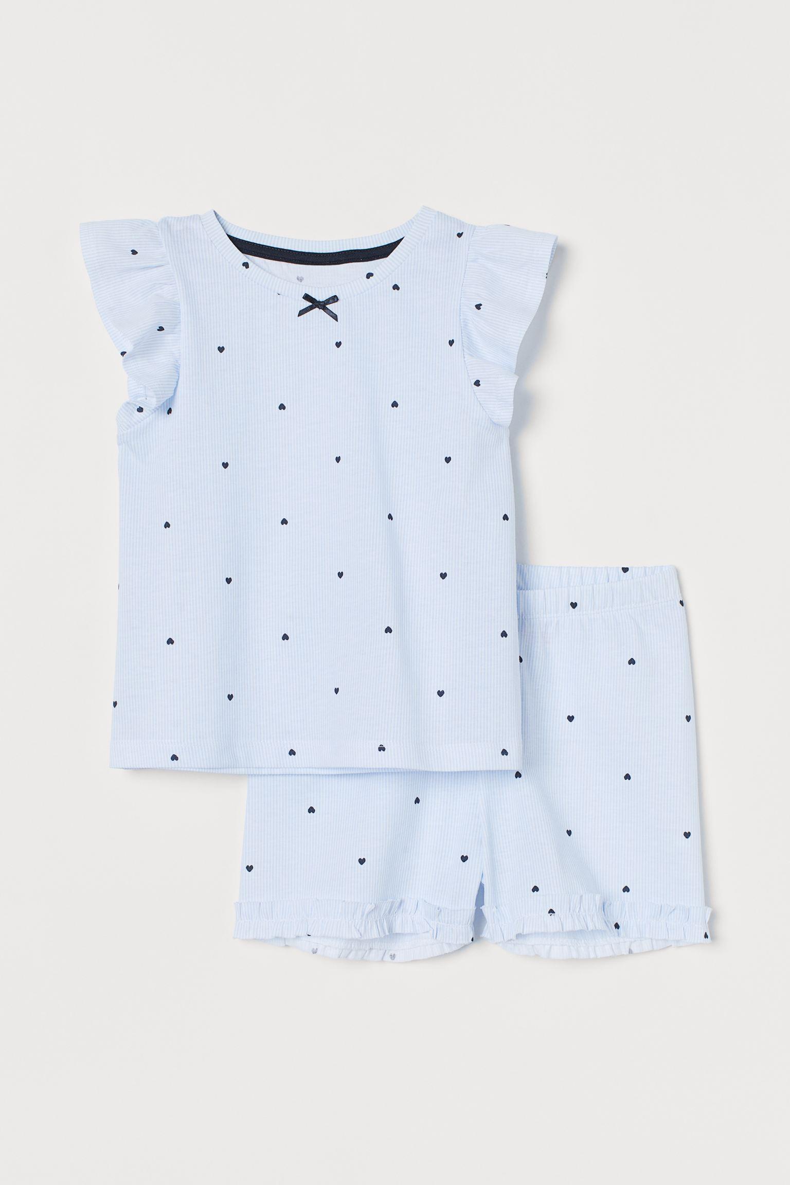 Pijama estampado en punto de algodón suave. Camiseta con mangas cortas de volante. Pantalón corto con cintura elástica y volante fruncido en el bajo.